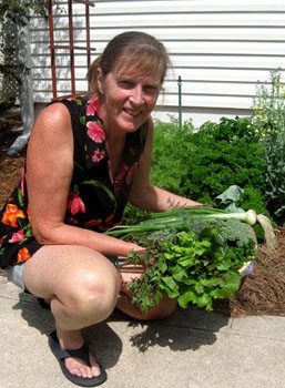 Ginny Stibolt with a bountiful spring harvest. The background is her wide-row garden.  