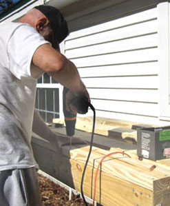 Pre-drilling for each nail is an important step in building the deck. Photo by Stibolt