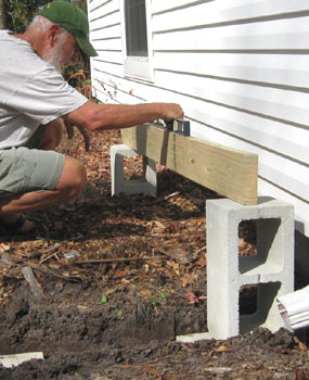Leveling between the footings at the ends of the deck using the cinder blocks to support a piece of wood to use for the level.  Photo by Stibolt.
